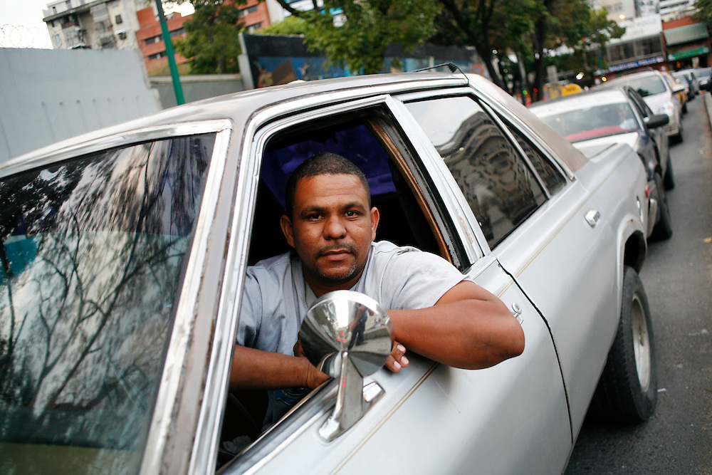A man sits in traffic in downtown Caracas.