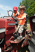 """Holden Miller, 5, and his cousin, Willem Fuller, 4, practice """"sharing"""" while pretending to drive an International Harvester tractor during the fourth annual International Student Farm Outing at the Schultz Family Farm in Cottage Grove, Wis., on June 24, 2012. Co-sponsored by the Schultz family and the University of Wisconsin-Madison International Student Services (ISS), the event introduced more than 100 UW-Madison international students and their families, and friends of the Schultz family to agricultural life in rural Wisconsin."""
