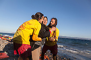 An Iraqi lady is helped to safety by Spanish volunteer lifeguards, after arriving on the Greek island of Lesvos.