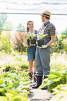 Gardeners discussing while holding potted plants at garden