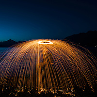 A man under the sparks of steel wool on the ocean