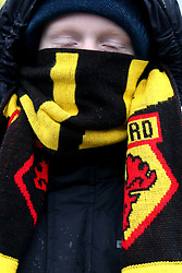 A Watford fan wraps up against the cold before the Premier League match at Vicarage Road, Watford.