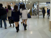 blurry view of two Japanese teenaged female students walking together