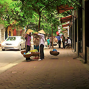 Three women vendors talking at the streets of Hanoi