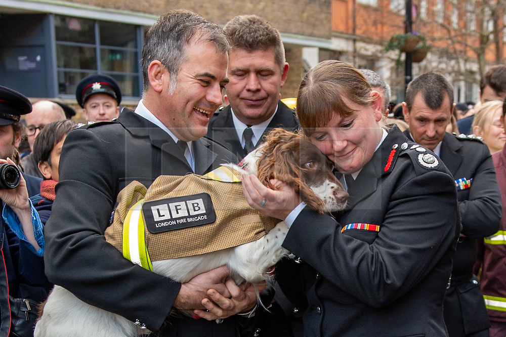 © Licensed to London News Pictures. 23/12/2019. London, UK. London Fire Brigade Commissioner Dany Cotton hugs a fire investigation dog as a Guard of Honour is held in London. Firefighters from across the UK and several from overseas attended the unofficial event outside the brigades headquarters in Union Street. Commissioner Cotton is retiring in the wake of the Grenfell Fire. Photo credit: Peter Manning/LNP