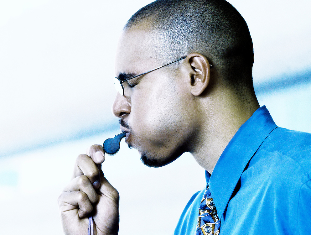 A businessman blowinga whistle.