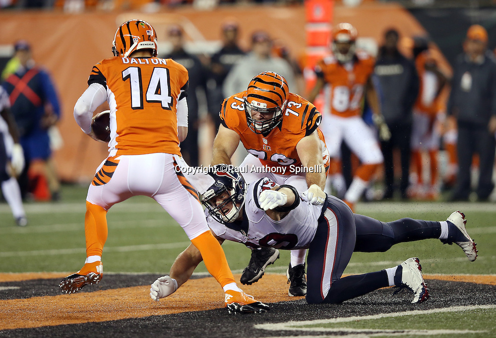 Houston Texans defensive end J.J. Watt (99) tries to tackle Cincinnati Bengals quarterback Andy Dalton (14) while being held, penalty on the play, by Cincinnati Bengals tackle Eric Winston (73) as Dalton runs the ball in the second quarter during the 2015 week 10 regular season NFL football game against the Houston Texans on Monday, Nov. 16, 2015 in Cincinnati. The Texans won the game 10-6. (©Paul Anthony Spinelli)