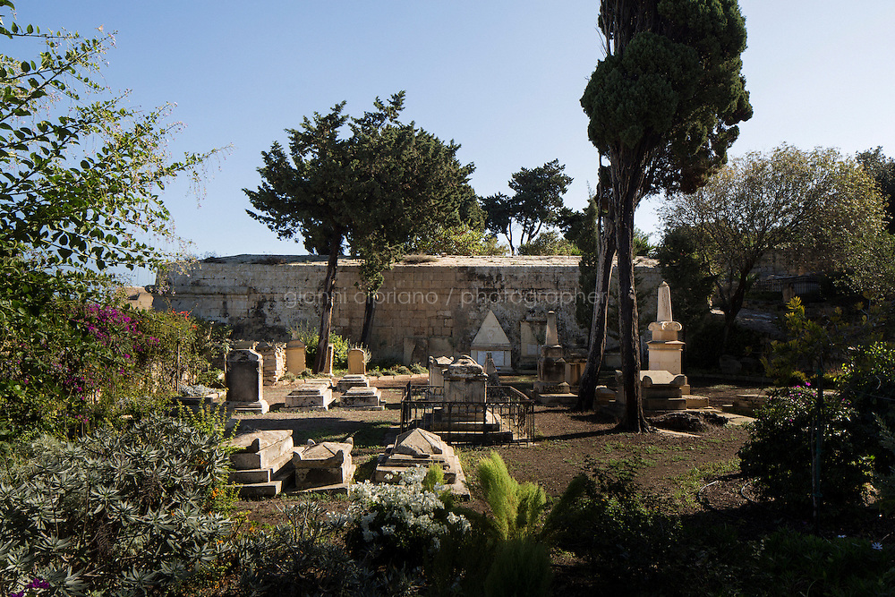 VALLETTA, MALTA - 3 November 2013: Graves at the Msida Garden of Rest in Valletta, Malta, on November 3rd 2013. The Garden was the main protestant cemetery or burial place in Malta from about 1806. The Garden of Rest lies in the Msida Bastion, which is so called because it overlooks Msida across the Harbour.<br /> <br /> Valleta was named after Jean Parisot de Valette of the Order of St. John of Jerusalem, who succeeded in defending the island from an Ottoman invasion in 1565, known as the Siege of Malta. The city was founded immediately after the end of the Siege of Malta to fortify the Order's position in Malta and bind the Knights to the island.