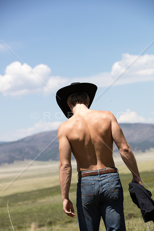 shirtless muscular cowboy on a ranch overlooking a mountain
