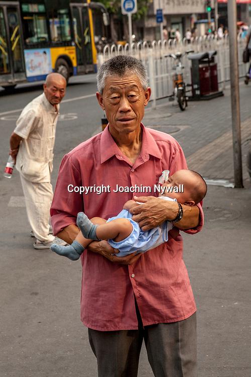 2011 08 10 Beijing China Peking Kina<br /> Gammal man med bebis i famnen p&aring; en gata i Beijing<br /> <br /> <br /> ----<br /> FOTO : JOACHIM NYWALL KOD 0708840825_1<br /> COPYRIGHT JOACHIM NYWALL<br /> <br /> ***BETALBILD***<br /> Redovisas till <br /> NYWALL MEDIA AB<br /> Strandgatan 30<br /> 461 31 Trollh&auml;ttan<br /> Prislista enl BLF , om inget annat avtalas.
