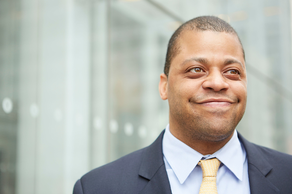 Lifestyle photograph of an African American realtor and businessman, standing in front of a modern looking glass wall, in Manhattan New York City