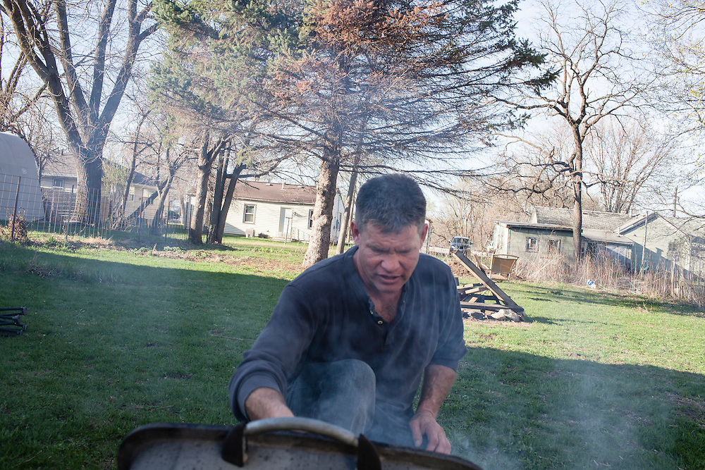 Steve McFarland grills pork chops in his back yard on Friday, March 23, 2012 in Webster City, IA.