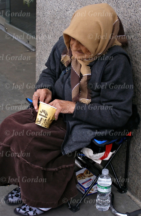 Homeless elderly streetperson begging for handouts in New York City. Homeless person living on the streets appearing depressed and appearing mentally ill shabbily dressed with evidence of poor hygiene..Without needed medication or consistent mental health care, persons with serious and persistent mental health problems may be forced to live on the streets in precarious circumstances...