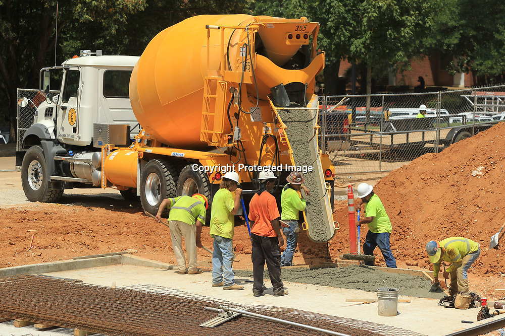 Construction crews work to pour sidewalks at the Student Union building on the University of Mississippi Campus on Monday afternoon in Oxford.