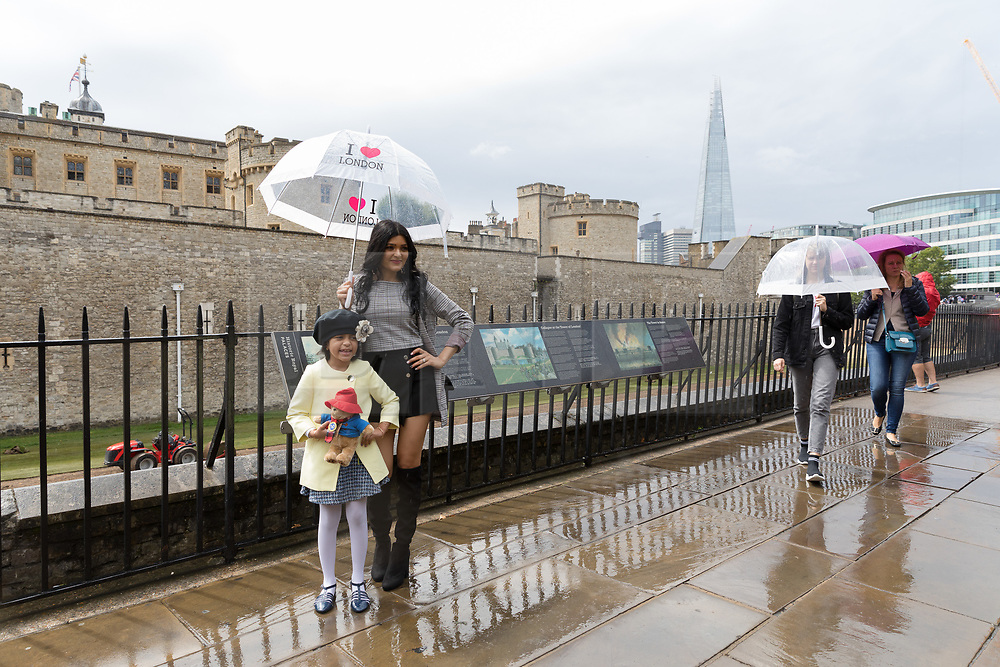 © Licensed to London News Pictures. 10/08/2018. London, UK.  Tourists are caught in a heavy rain shower and wet weather near the Tower of London at lunchtime today [permission given by mother and child on left].  Photo credit: Vickie Flores/LNP