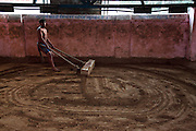 A wrestler drags the 30kg log flattening the traditional soil ring. For almost 3000 years loincloth clad duels on mud have transfixed spectators across India. Yet wrestling in India is a sport in transition. In 2004 the Indian Fighters Federation tried to prohibit the practice of traditional mud wrestling, claiming that for India to compete at an international level fighters must train using mats. Whilst competing on mud can earn good money for a wrestler at events called dungals in India's countryside, the techniques are starkly different. ..The Guru Hanuman Akhara, a wrestling school in Old Delhi, is the epicentre of this ancient wrestling tradition as it begins to enter the modern world. Now training fighters on both mats and mud the school has produced hundreds of champions at both domestic and international level...Established in 1925, making it the oldest in India, it was in 1955 that Vijay Pal, or Guru Hanuman as he later became known, took over the coaching...Born to a poor family in the desert state of Rajasthan he chose never to marry and instead dedicated his whole life to wrestling, becoming a legend, who created a model for modern Indian wrestling by combining traditional Indian wrestling called Kushti with international standards. His statue and mausoleum stands overlooking the outer courtyard of the school.....