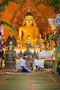 """29 JUNE 2014 - DAN SAI, LOEI, THAILAND:  A man meditates in Wat Ponchai during the """"Ghost Festival."""" Phi Ta Khon (also spelled Pee Ta Khon) is the Ghost Festival. Over three days, the town's residents invite protection from Phra U-pakut, the spirit that lives in the Mun River, which runs through Dan Sai. People in the town and surrounding villages wear costumes made of patchwork and ornate masks and are thought be ghosts who were awoken from the dead when Vessantra Jataka (one of the Buddhas) came out of the forest. On the last day of the festival people participate in merit making ceremonies at the Wat Ponchai in Dan Sai and lead processions through town soliciting donations for the temple.    PHOTO BY JACK KURTZ"""