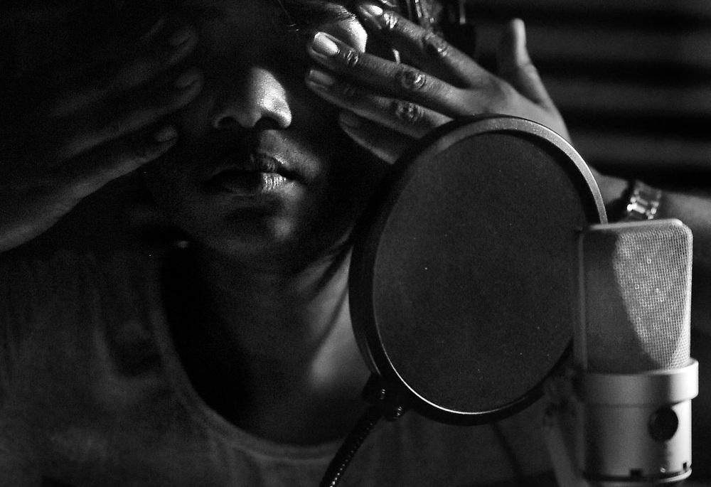 Nekita Waller rubs her eyes inside the booth after hours of recording vocals in the studio.
