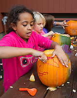 Lily, Bianca and Riley carve out pumpkins for Saturday's Pumpkin Fest at the Laconia Boys and Girls Club on Tuesday afternoon.  (Karen Bobotas/for the Laconia Daily Sun)