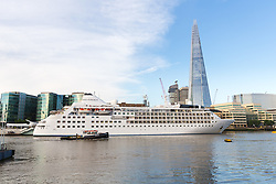 © Licensed to London News Pictures. 01/08/2017. LONDON, UK.  Silver Wind, a huge 514 feet long, 17,400 ton cruise liner leaves London passing the Shard before travelling under Tower Bridge this morning after a brief visit, towed backwards by two tugs. Silver Wind carries just 296 passengers and its owner, Silversea claim that the ship has amongst the highest space-to-guest ratios in the cruise ship industry, with the largest suites measuring 1,314 square feet. Tickets cost thousands of pounds, but all guest expenses, even champagne are included in the price. Environmentalists claim the pollution created by giant cruise ships outweigh their economic benefits. The Port of London Authority (PLA) are conducting a work programme during 2017 to monitor air quality and pollution caused by river traffic on the River Thames.  Photo credit: Vickie Flores/LNP