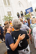 Residents embrace during a memorial service for the Charleston Nine outside the Mother Emanuel African Methodist Episcopal Church on the anniversary of the mass shooting June 18, 2016 in Charleston, South Carolina. Nine members of the church community were gunned down during bible study inside the church on June 17, 2015.