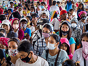 24 JANUARY 2018 - GUINOBATAN, ALBAY, PHILIPPINES: People affected by the eruption of the Mayon volcano line up for government provided financial assistance in Guinobatan. Many of the people were wearing breathing filters because a volcanic ash fall. The Mayon volcano continued to erupt Tuesday night and Wednesday forcing the Albay provincial government to order more evacuations. By Wednesday evening (Philippine time) more than 60,000 people had been evacuated from communities around the volcano to shelters outside of the 8 kilometer danger zone. Additionally, ash falls continued to disrupt life beyond the danger zones. Several airports in the region, including the airport in Legazpi, the busiest airport in the region, are closed indefinitely because of the amount of ash the volcano has thrown into the air.    PHOTO BY JACK KURTZ
