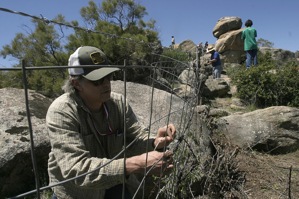 'Minuteman Project' volunteer secures barbed wire to fence posts as part of a project to build a privately funded fence along the US/Mexico border, to keep out undocumented immigrants, in Boulevard, California April 29, 2006. There is a fence erected along part of the border in the area, but the 'Minuteman Project' wanted to bridge the gaps with a privately financed fence of their own built between the government built sections. More than 100 volunteers participated in the daylong event. Boulevard is about 65 miles (104.6 km) east of downtown San Diego.....