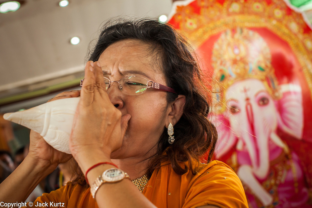 "29 SEPTEMBER 2012 - NAKORN NAYOK, THAILAND:  A woman blows a conch horn during observances of Ganesh Ustav at Wat Utthayan Ganesh, a temple dedicated to Ganesh in Nakorn Nayok, about three hours from Bangkok. Many Thai Buddhists incorporate Hindu elements, including worship of Ganesh into their spiritual life. Ganesha Chaturthi also known as Vinayaka Chaturthi, is the Hindu festival celebrated on the day of the re-birth of Lord Ganesha, the son of Shiva and Parvati. The festival, also known as Ganeshotsav (""festival of Ganesha"") is observed in the Hindu calendar month of Bhaadrapada, starting on the the fourth day of the waxing moon. The festival lasts for 10 days, ending on the fourteenth day of the waxing moon. Outside India, it is celebrated widely in Nepal and by Hindus in the United States, Canada, Mauritius, Singapore, Thailand, Cambodia, Burma , Fiji and Trinidad & Tobago.     PHOTO BY JACK KURTZ"