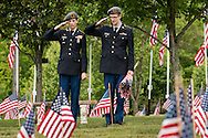 Goshen, New York - Minisink Valley High School Army JROTC cadets salute after placing American flags by a veterans' graves at the Orange County Veteran's Cemetery in preparation for Memorial Day on May 24, 2016.
