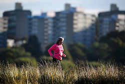 © Licensed to London News Pictures. 09/10/2016. London, UK. A woman jogging on a bright autumnal morning in Richmond Park, London. . Photo credit: Ben Cawthra/LNP