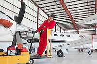 Young male aviation mechanic repairing airplane in airplane hangar