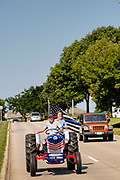 "08 AUGUST 2020 - WEST DES MOINES, IOWA: GARY LEFFLER, from West Des Moines, drives a red, white, and blue tractor down Mills Civic Parkway during a rally to support law enforcement in West Des Moines. About 100 people gathered at the West Des Moines Law Enforcement Center to rally in support of law enforcement. The rally was organized by ""Uplifting Our Police,"" a local organization that supports law enforcement. They rallied at Des Moines Police headquarters in July. They are planning similar rallies at police stations in the Des Moines metropolitan area.     PHOTO BY JACK KURTZ"