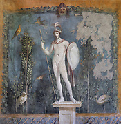 God Mars on a plinth with lance and shield, in a garden of plants and birds, fresco, in the peristyle of the House of Venus in the Shell, or Casa della Venere in Conchiglia, in the Parco Archeologico di Pompei, or Archaeological Park of Pompeii, Campania, Italy. Pompeii was a Roman city which was buried in ash after the eruption of Vesuvius in 79 AD. The site is listed as a UNESCO World Heritage Site. Picture by Manuel Cohen