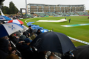 Umbrellas are up in the stands and covers are being brought on as a shower passes over during the delay in play during the Specsavers County Champ Div 1 match between Somerset County Cricket Club and Essex County Cricket Club at the Cooper Associates County Ground, Taunton, United Kingdom on 25 September 2019.