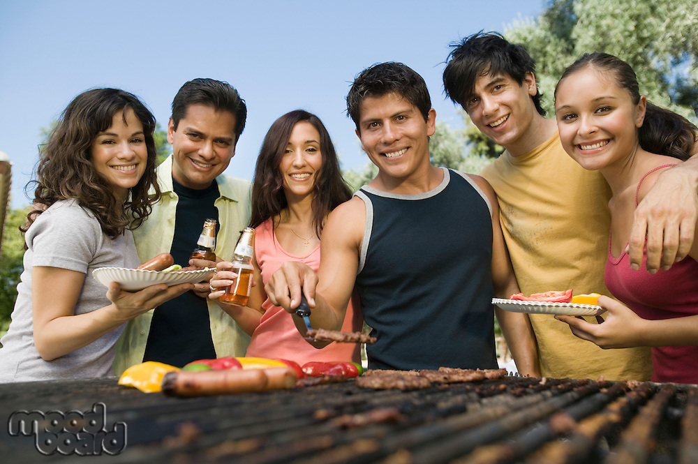 Group of young people around outdoor grill.