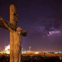 USA, Louisiana, Baton Rouge, Statue of Jesus Christ in graveyard near petrochemical plant