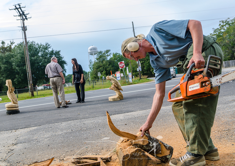 Alabama chainsaw artist James Seal carves a whooping crane as his wife, Miranda Seal, tries to sell his artwork to a bystander in Coden, Ala. The couple says they need health insurance, but they have not yet explored their options through the Obamacare health care exchange. (Photo by Carmen K. Sisson/Cloudybright)