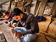 05 MARCH 2017 - KATHMANDU, NEPAL: A craftsman carves wood that will be used to repair the Itum Baha temple, an 11th Century Hindu temple damaged in the 2015 earthquake. Much of Kathmandu is now a construction site because of rebuilding  two years after the earthquake of 25 April 2015 that devastated Nepal. In some villages in the Kathmandu valley workers are working by hand to remove ruble and dig out destroyed buildings. About 9,000 people were killed and another 22,000 injured by the earthquake. The epicenter of the earthquake was east of the Gorka district.     PHOTO BY JACK KURTZ
