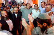 Men singing and dancing in Hebron's Jewish community. Some six hundred Jews live in the heart of the old city surrounded by over 160,000 Palestinian inhabitants.<br /> Hebron, Israel. 04/11/2007