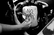 Demonstrators writing slogans on one of the participants body during the protest outside Bechtel's corporate headquarter, San Francisco, 2004
