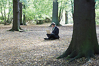 Mid adult business man sitting cross-legged in middle of forest working on laptop