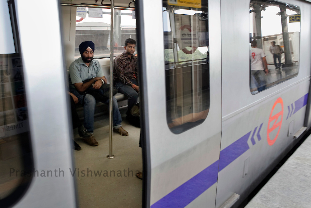 """Arvider Singh, 29, (with turban) travels inside a metro train from the Central Secratariat station using the """"Yellow Line"""" route of the Delhi Metro network in New Delhi, India, on Friday, October 22, 2010. Photographer: Prashanth Vishwanathan/HELSINGIN SANOMAT"""