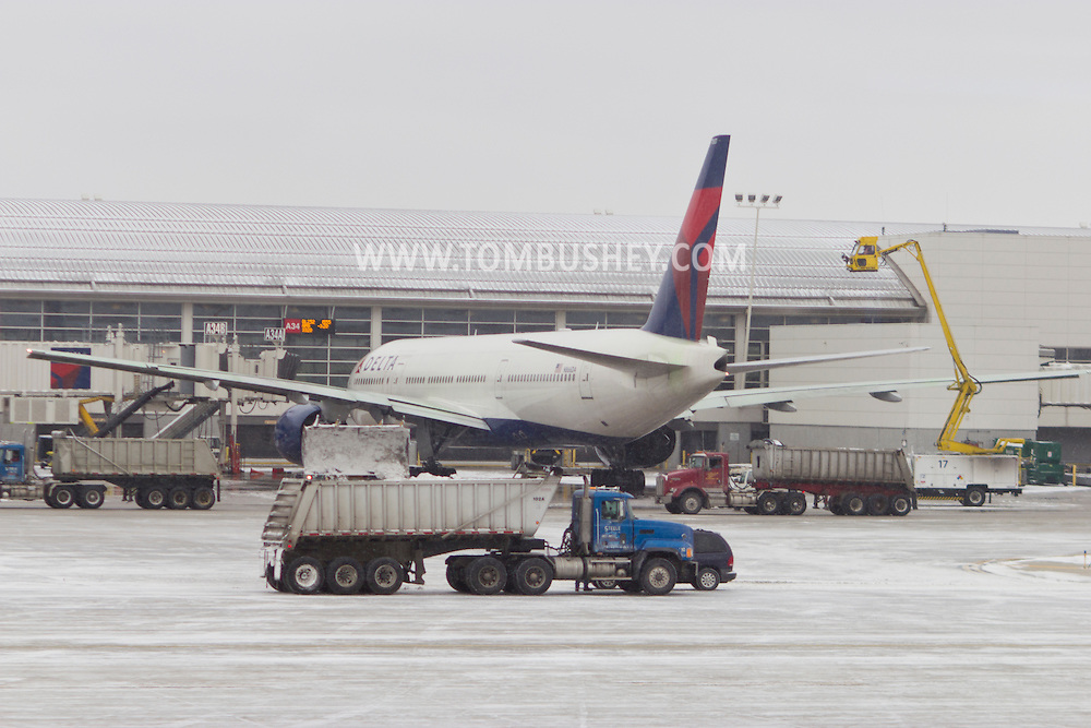 Detroit, Michigan - A front-end loader dumps now into the back of a truck on the tarmac at Detroit Metropolitanl Airport on Feb. 3, 2013. A Delta Airlines Boeing 777-232ER is being deiced in the background.