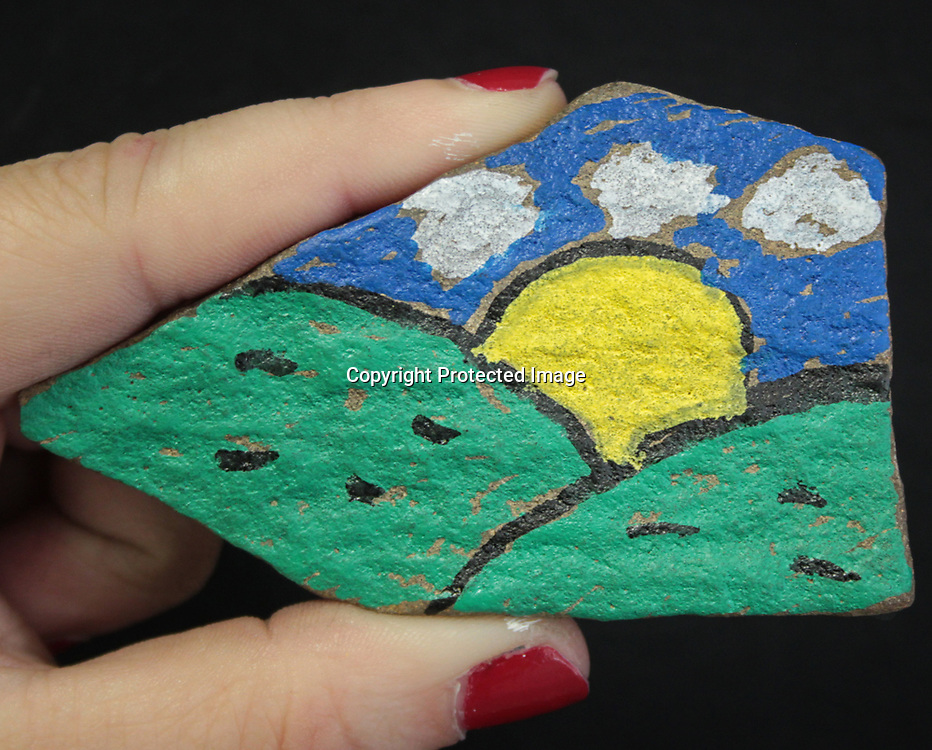ADAM ARMOUR I BUY AT PHOTOS.ITAWAMBATIMES.COM<br /> Fulton&rsquo;s Beth Stovall displays a rock, painted with an image of the sun cresting a folkloric hillside, which she plans to hide somewhere in downtown Fulton. Stovall recently created a Facebook &ldquo;treasure hunting&rdquo; group, Itawamba Rocks, which creates, hides and hunts painted stones.