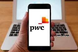 Using iPhone smartphone to display logo of PWC , PricewaterhouseCoopers , the multinational professional services network