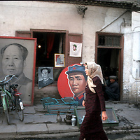 KASHGAR, 1 OCTOBER 2001 : A Uighur woman walks past an antiques store that sells Mao Zedong souvenirs.. Uighur muslims in southern Xinjiang province lead very basic lifestyles and have an average monthly income of about 50 US$.. (photo by: katharina hesse/Grazia Neri).