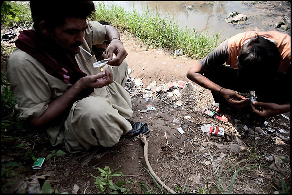 "Heroin smokers consume their dose nearby a polluted river. Islamabad Pakistan, on friday, August 29 2008.....""Pakistan is one of the countries hardest hits by the narcotics abuse into the world, during the last years it is facing a dramatic crisis as it regards the heroin consumption. The Unodc (United Nations Office on Drugs and Crime) has reported a conspicuous decline in heroin production in Southeast Asia, while damage to a big expansion in Southwest Asia. Pakistan falls under the Golden Crescent, which is one of the two major illicit opium producing centres in Asia, situated in the mountain area at the borderline between Iran, Afghanistan and Pakistan itself. .During the last 20 years drug trafficking is flourishing in the Country. It is the key transit point for Afghan drugs, including heroin, opium, morphine, and hashish, bound for Western countries, the Arab states of the Persian Gulf and Africa..Hashish and heroin seem to be the preferred drugs prevalence among males in the age bracket of 15-45 years, women comprise only 3%. More then 5% of whole country's population (constituted by around 170 milion individuals),  are regular heroin users, this abuse is conspicuous as more of an urban phenomenon. The substance is usually smoked or the smoke is inhaled, while small number of injection cases have begun to emerge in some few areas..Statistics say, drug addicts have six years of education. Heroin has been identified as the drug predominantly responsible for creating unrest in the society."""