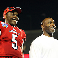 Louisville Cardinals quarterback Teddy Bridgewater (5) and head coach Charlie Strong celebrate on the podium after the NCAA Football Russell Athletic Bowl football game between the Louisville Cardinals and the Miami Hurricanes, at the Florida Citrus Bowl on Saturday, December 28, 2013 in Orlando, Florida. Louisville won the game by a score of 36-9. (AP Photo/Alex Menendez)