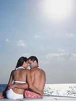 Young couple embracing on cushions on yacht back view