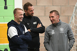 Celtic's Leigh Griffiths (left) and manager Brendan Rodgers (right) with Street Soccer founder and CEO David Duke (centre) watch the men and women Street Soccer teams during a special training session at Lennoxtown, Glasgow.